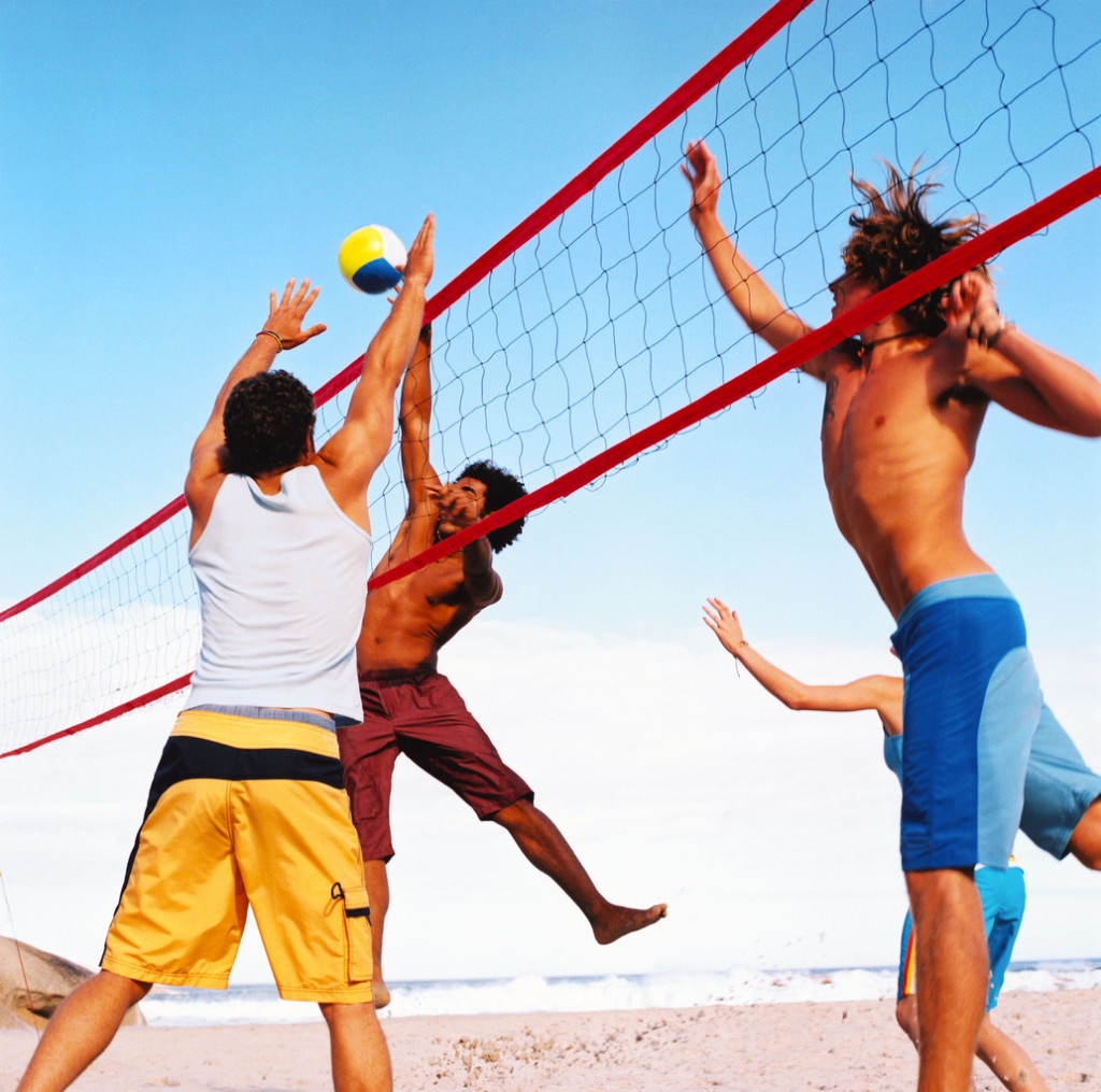 Group of People Playing Volleyball on the Beach --- Image by © Royalty-Free/Corbis